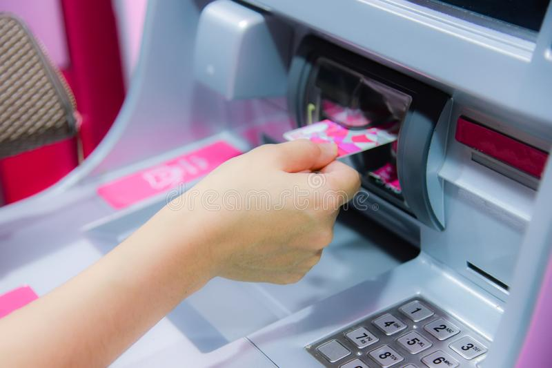 Finanza, soldi, concetto della banca - mano femminile con contanti e carta di credito alla macchina di bancomat fotografie stock