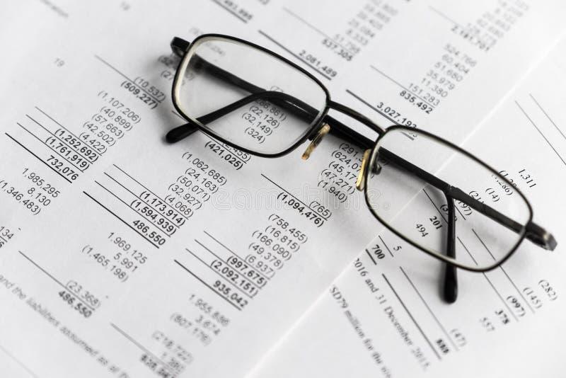 Finanzanalyse - Gewinn- und Verlustrechnung, Unternehmensplan mit Glas lizenzfreie stockfotografie