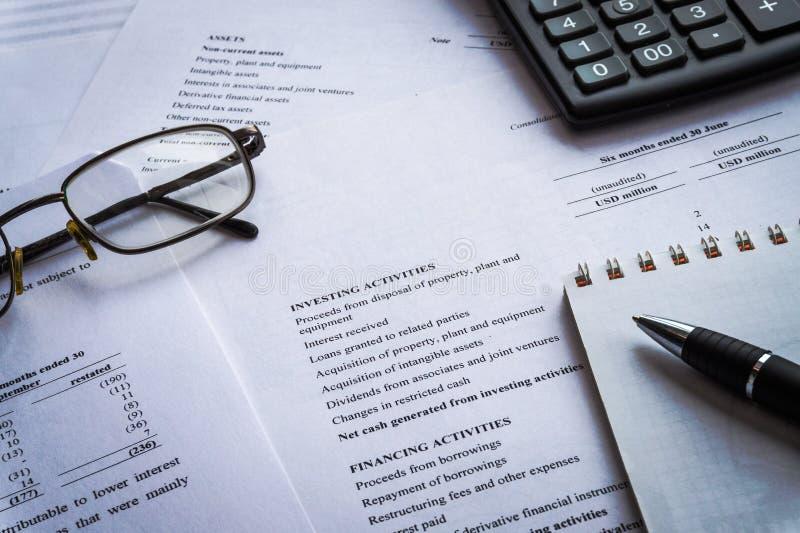 Finanzas, análisis financiero, hoja de cálculo de las cuentas que considera con los vidrios de la pluma y calculadora imagen de archivo
