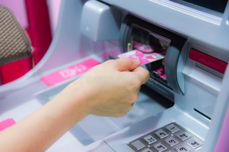 Finanzas, dinero, concepto del banco - mano femenina con efectivo y tarjeta de crédito en la máquina de la atmósfera fotos de archivo