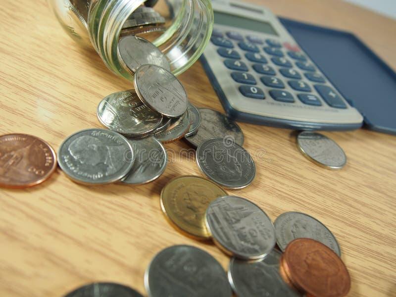 Finanzas, negocio, pila de monedas, dinero tailandés en la cristalería, calculadora en el fondo de madera fotos de archivo