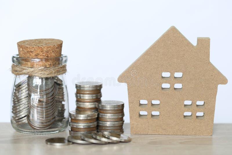 Finanzas, pila de dinero de las monedas y casa modelo en fondo del wtite, la inversión empresarial y propiedades inmobiliarias imágenes de archivo libres de regalías
