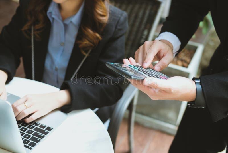 Finanzberater, der mit Taschenrechner u. Computer im Büro arbeitet stockbilder