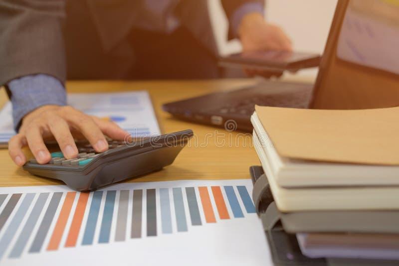 Finanzberater, der mit Taschenrechner u. Handy arbeitet Accoun stockfoto