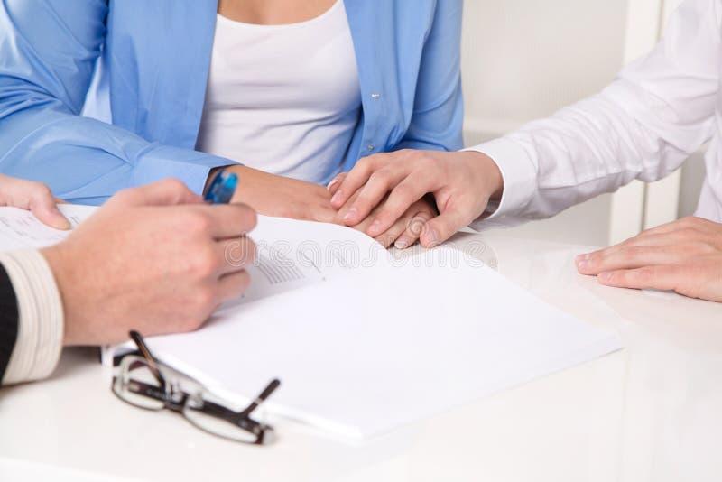 Finanzberater erklärt einen Vertrag - junges Paar lizenzfreie stockbilder