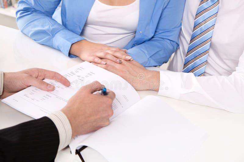 Finanzberater erklärt einen Vertrag - junges Paar lizenzfreie stockfotos