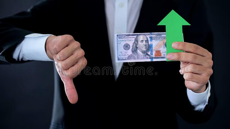 Finanzberater mit den Dollarbanknoten, die unten Daumen und grünen Pfeil zeigen lizenzfreies stockbild