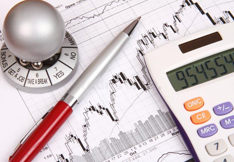 Finanzdiagramm mit einem Rechner und einer roten Feder lizenzfreie stockfotos