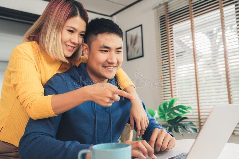 Finanze in carico delle giovani coppie asiatiche, esaminando i loro conti bancari facendo uso del computer portatile e del calcol fotografia stock