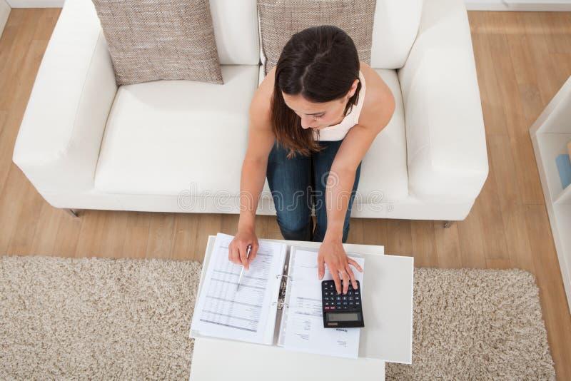 Finanze domestiche calcolarici della donna sicura alla tavola immagini stock