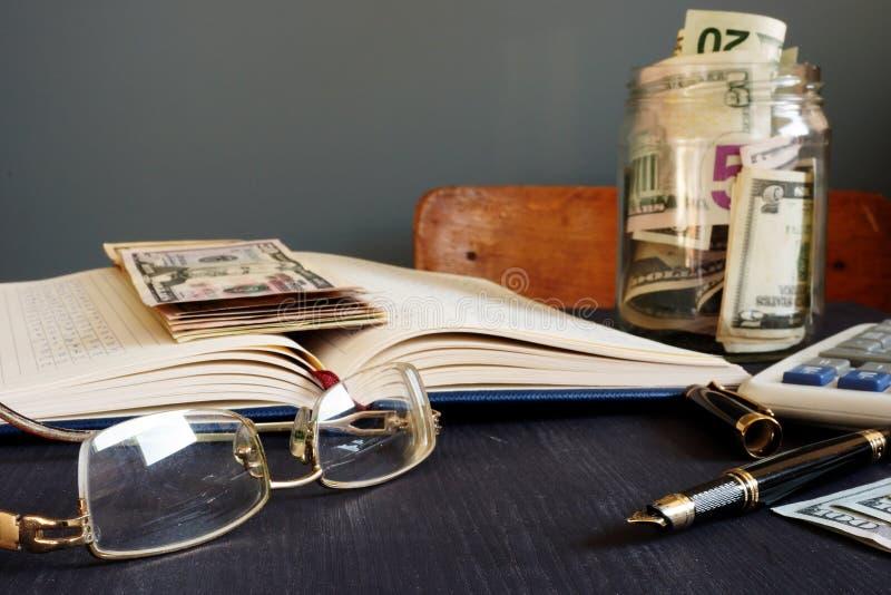 Finanze domestiche Prenoti con le figure ed il barattolo finanziari con soldi risparmio fotografia stock libera da diritti