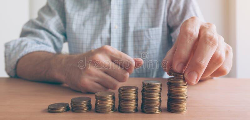 Finanze e stanziare, uomo d'affari che impila le monete immagini stock libere da diritti
