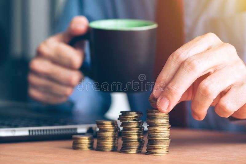 Finanze e stanziare, uomo d'affari che impila le monete immagine stock libera da diritti