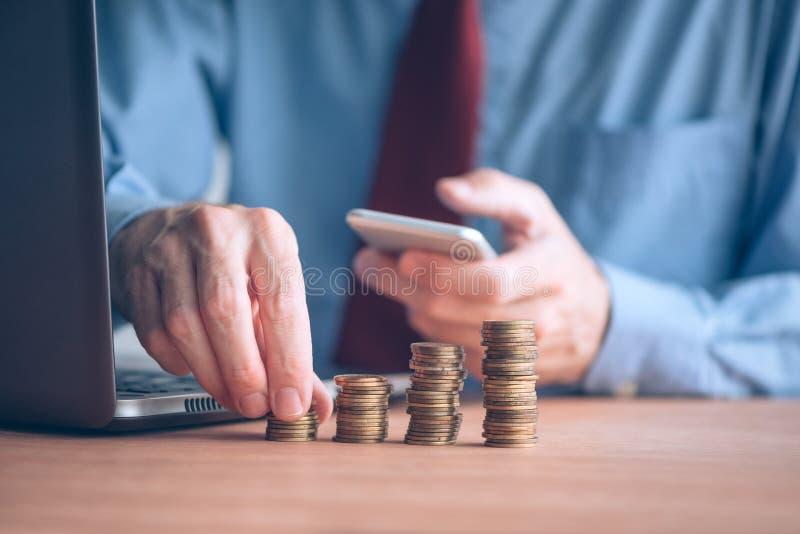 Finanze e stanziare, uomo d'affari che impila le monete immagini stock