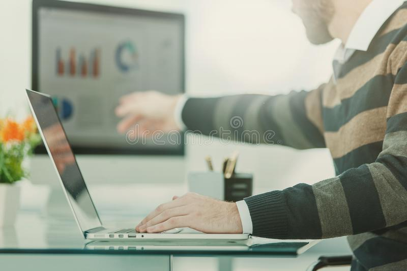 Finanzi lo specialista che lavora al computer portatile con i grafici e gli schemi finanziari di vendita fotografia stock libera da diritti
