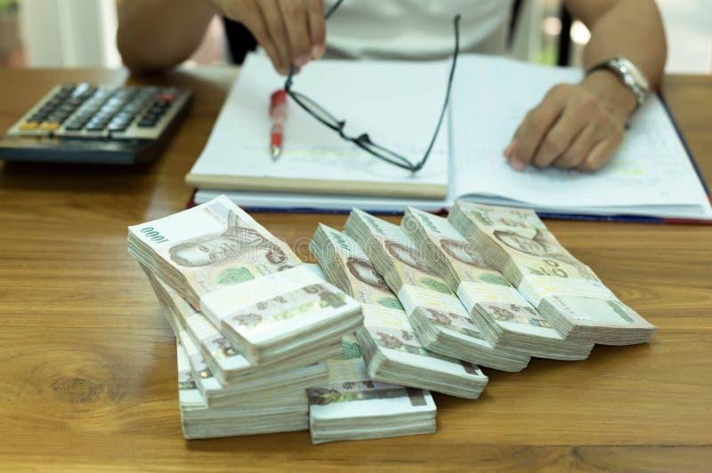 Finanzkonzept Geschäftsmann, der Gläser mit Stapel von thailändischem hält lizenzfreies stockbild