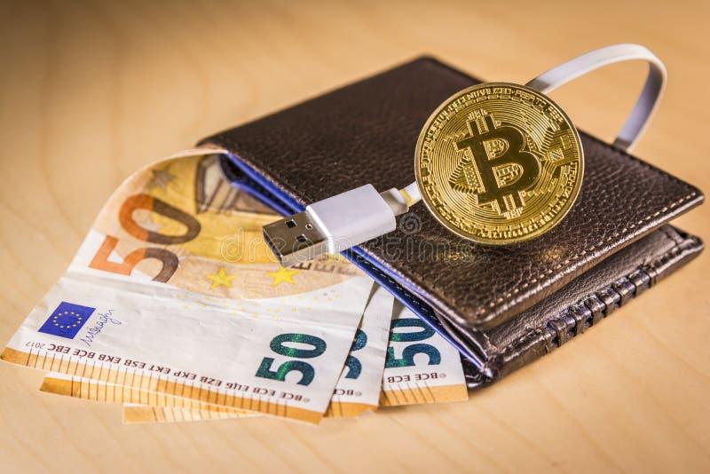 Finanzkonzept mit goldenem Bitcoin über einer Geldbörse mit Eurorechnungen und USB verkabeln stockfoto