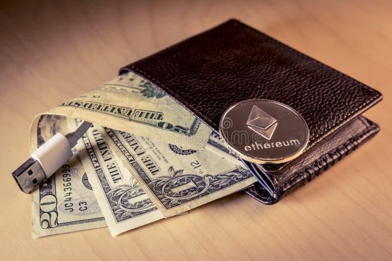 Finanzkonzept mit körperlichem ethereum über einer Geldbörse mit US-Dollars und USB verkabeln stockbild