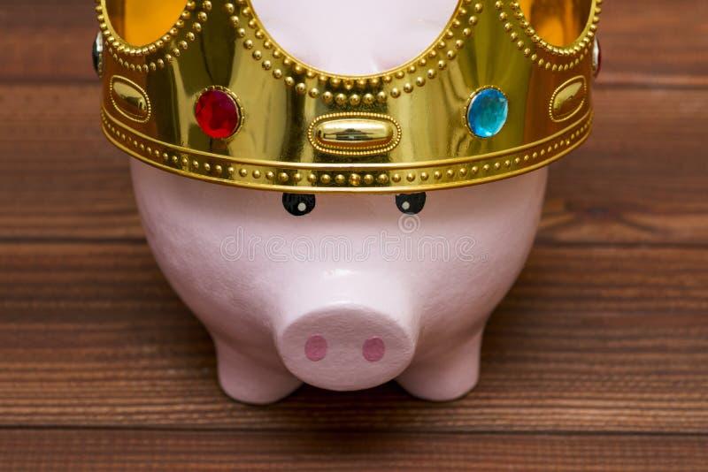 Finanzsieger oder König des Geldspareinlagenkonzeptes, lächelndes glückliches rosa Sparschwein, das eine goldene Krone auf hölzer lizenzfreie stockfotos