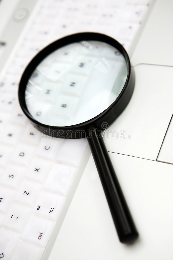 Find. Magnifying glass on a laptop keyboard - concept for search/find. Shallow dof royalty free stock images