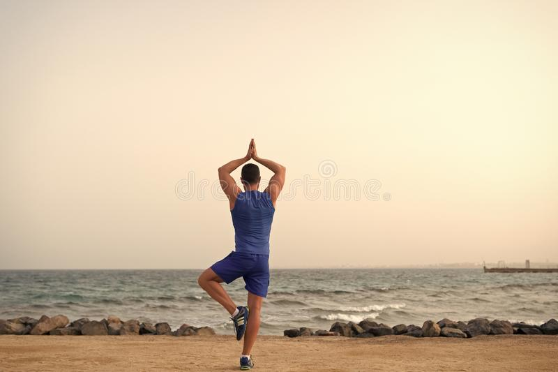 Find balance and unite with nature. Yoga practice helps find harmony and balance. Man practicing yoga sea beach. Background. Peaceful place. Reached peace of royalty free stock image