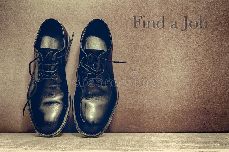 Find a Jobt on brown board and work shoes on wooden floor stock images