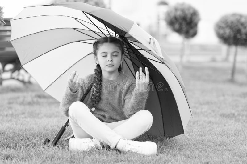Find peaceful private space to relax. Under big umbrella. Girl child long hair meditate park under umbrella. Stay stock photography