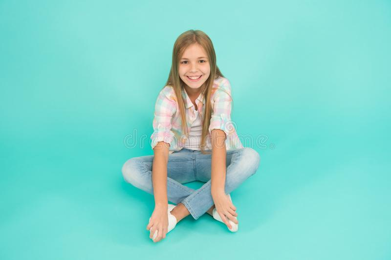 Find place to relax. Girl happy face sit on floor attentive looking at camera turquoise background. Kid girl with long. Hair relaxing. Just relaxing here. Feel royalty free stock photos