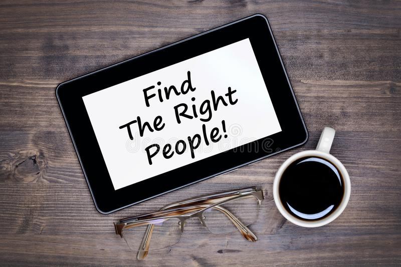 Find the right people! Text on tablet device on table royalty free stock photo