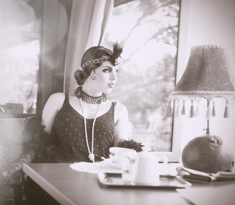 Find Similar Get a Comp Save to LightboxRetro Woman 1920s - 19. Black and White Portrait of The Beautiful Retro woman Drinking Tea in the Cafe in Black Lace and royalty free stock image