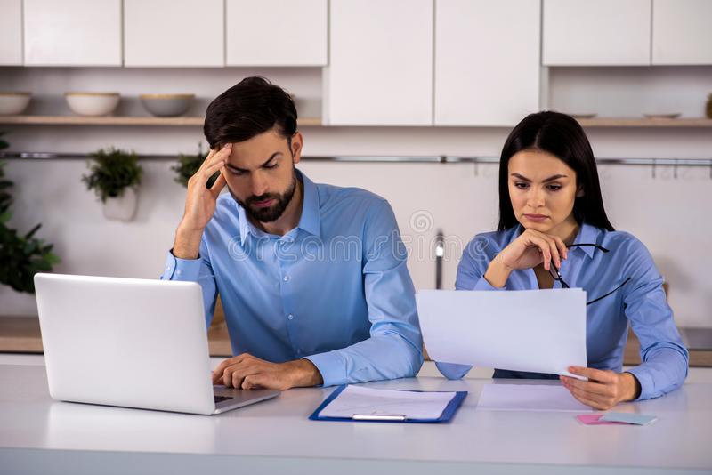 Troubled young business colleagues sitting at the table stock images