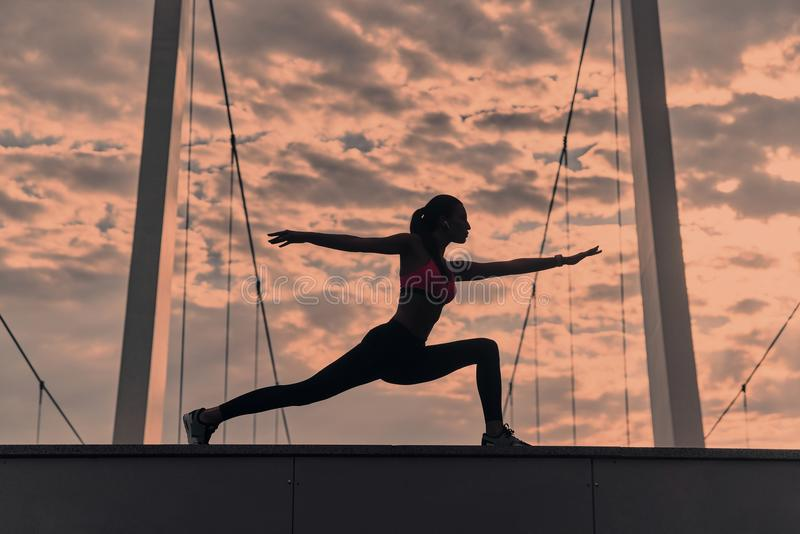 Find your balance. Modern young woman in sports clothing stretching while warming up outdoors royalty free stock photos