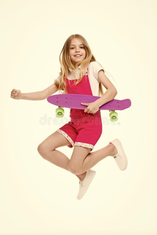 Find your freedom Small girl jump with skate board isolated on white. Child skater smile with longboard. Skateboard kid. In pink jumpsuit. Sport activity and royalty free stock images