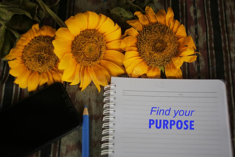 Find your purpose inspirational words on notebook paper with yellow flowers on classic tablecloth background. Inspirational motivational quote - find your stock images