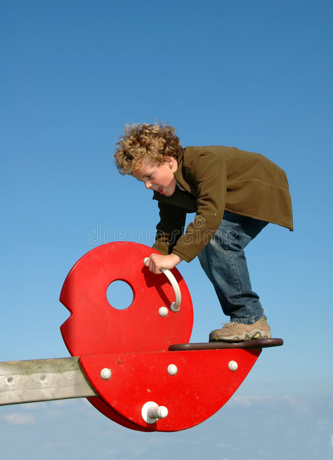 Finding Balance. Boy (7) trying to find his balance on a see-saw royalty free stock images