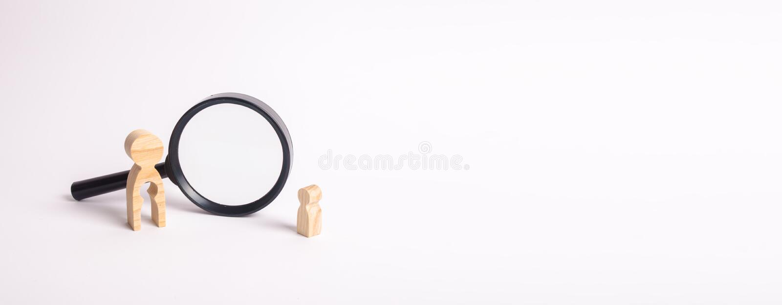 Finding a child, the adoption of children. Mother lost her baby and is now looking for him. A wooden figure of a woman and a child stands near the magnifying stock photos