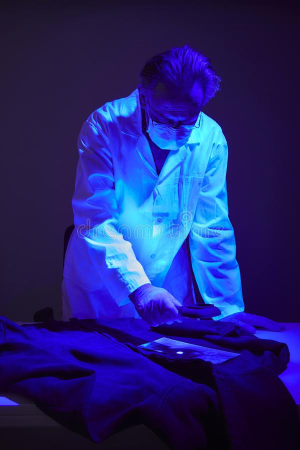 Finding of evidences on criminal`s shirt under UV light by technician. Checking of suspected person dress by forensic specialist in crime lab stock photography