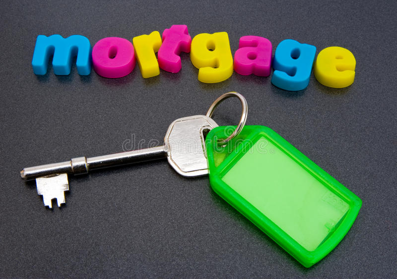Finding a mortgage. The word mortgage in colorful lower case letters with the key to a new home beneath it. The image is isolated against a dark background royalty free stock photos