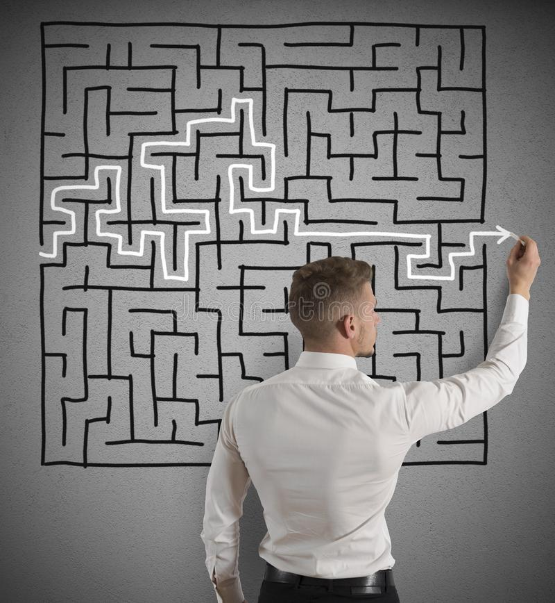 Finding the solution. Businessman finding the solution of a maze royalty free stock photography