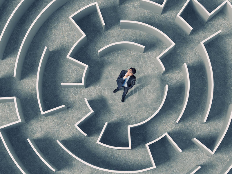 Finding the solution. Top view of successful businessman standing in center labyrinth stock photo