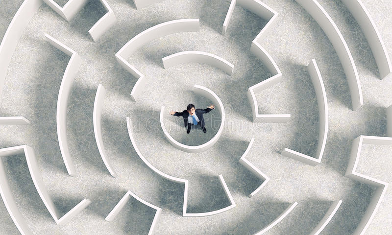 Finding the solution. Top view of successful businessman standing in center of labyrinth royalty free stock images
