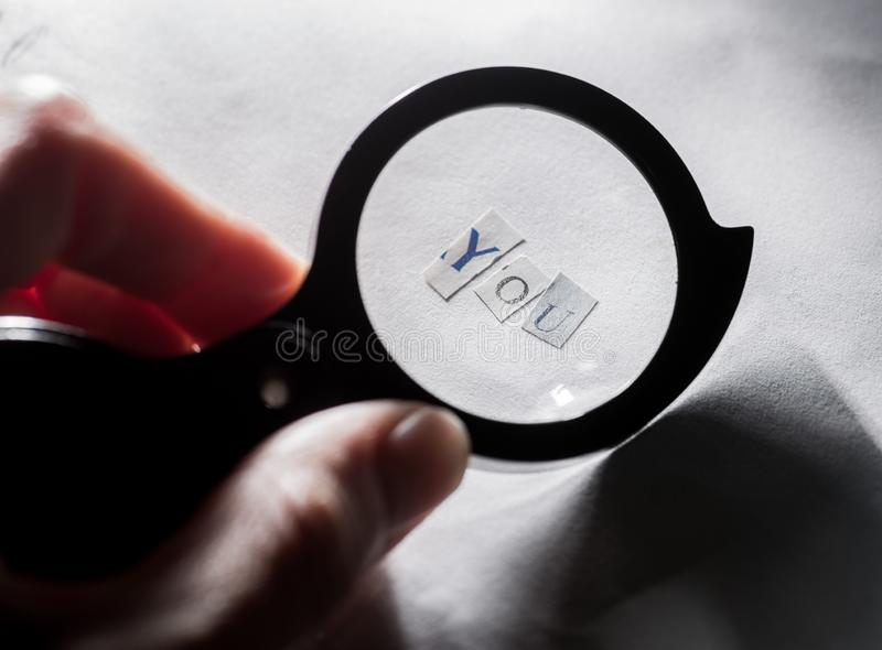 Finding yourself. Word `you` of letters on paper through a magnifying glass stock image