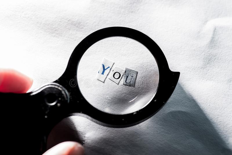 Finding yourself. Word `you` of letters on paper through a magnifying glass royalty free stock images