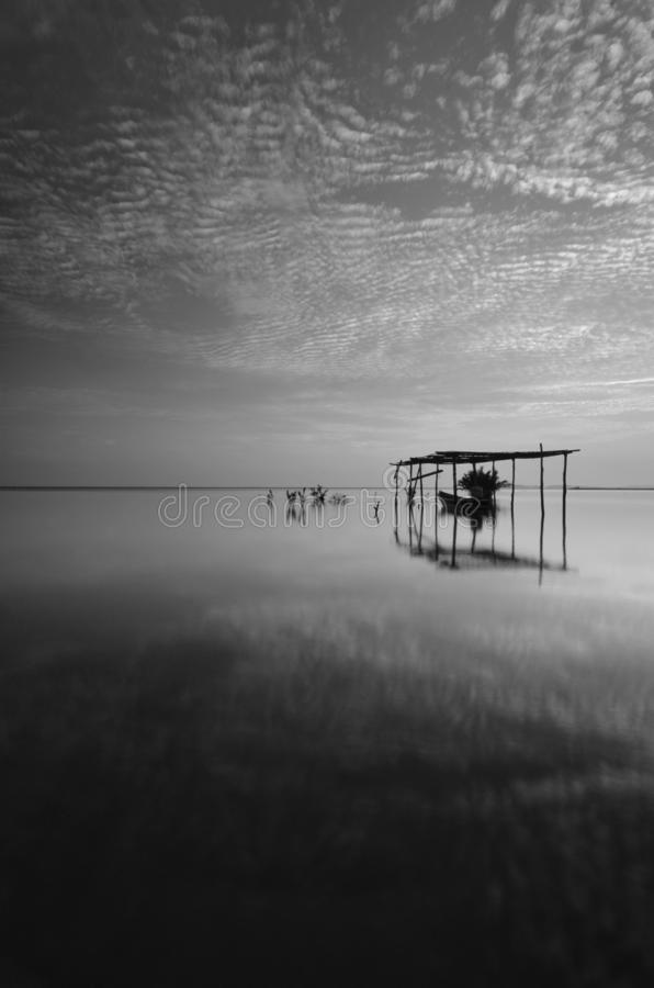 Fine art Black & white image of beautiful landscape of the beach at morning. Fisherman boat and clouds reflecting in the water. royalty free stock photo
