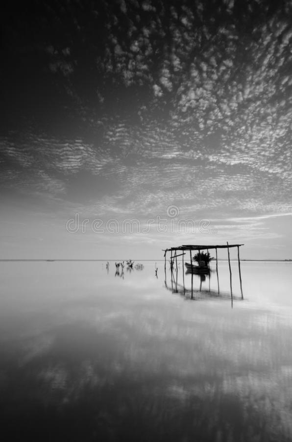 Fine art Black & white image of beautiful landscape of the beach at morning. Fisherman boat and clouds reflecting in the water. stock photos