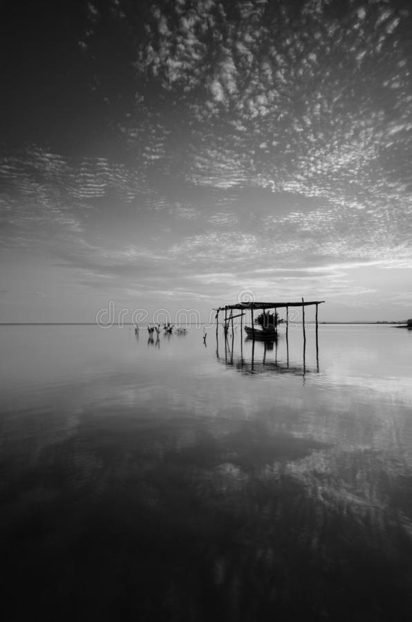 Fine art Black & white image of beautiful landscape of the beach at morning. Fisherman boat and clouds reflecting in the water. stock photo