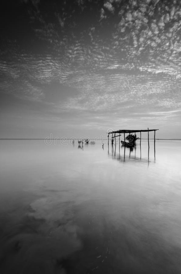 Fine art Black & white image of beautiful landscape of the beach at morning. Fisherman boat and clouds reflecting in the water. stock image
