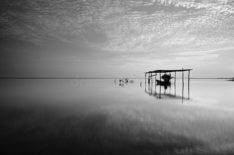 Fine art Black & white image of beautiful landscape of the beach at morning. Fisherman boat and clouds reflecting in the water. stock images