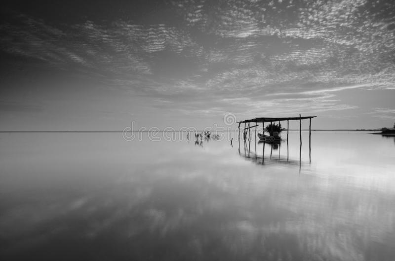 Fine art Black & white image of beautiful landscape of the beach at morning. Fisherman boat and clouds reflecting in the water. stock photography