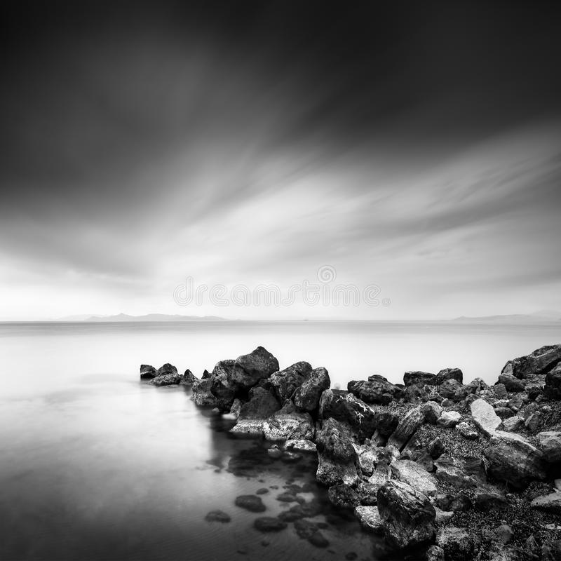 Rocky pier in Athens, Greece. Fine Art, Black and White, Long exposure photograph of a rocky pier in the sea stock images